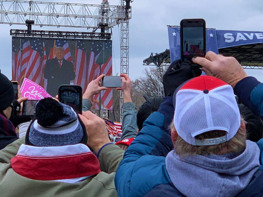 Mob at the US Capitol watches Trump on a giant screen. photo by Voice of America via Wikimedia Commons