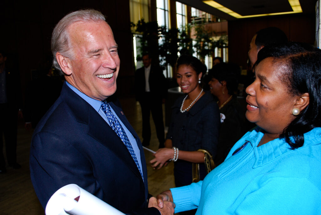 Joe Biden smiling broadly and warmly while greeting people